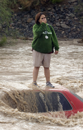 Woman trapped on top of her car in flash flood