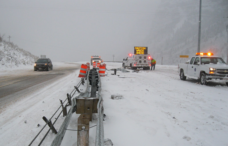 Emergency vehicles on a snowy mountain road
