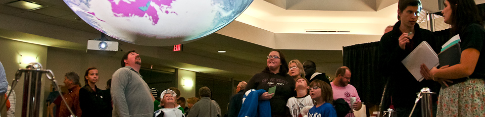 Visitors and Science on a Sphere in the atrium of the National Weather Center