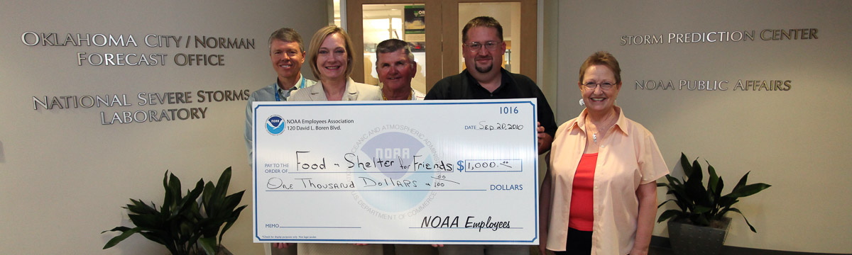 NOAA employees at the National Weather Center presenting a check to a local charity