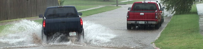 truck driving through street flooding