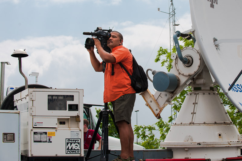 Media cameraman shooting from atop a mobile radar vehicle