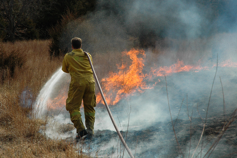firefighter fighting grassfire