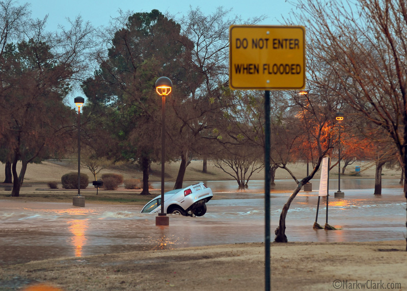 car driven into sinkhole masked by floodwaters