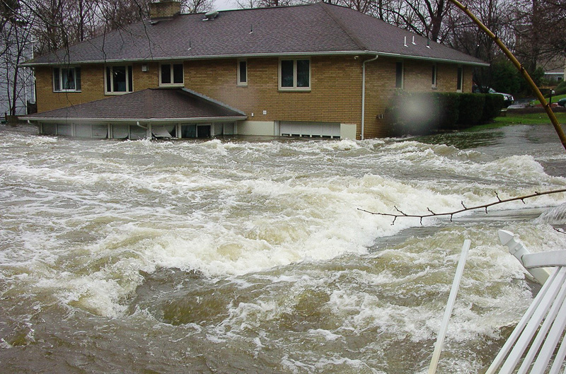 flash flood waters rushing past house